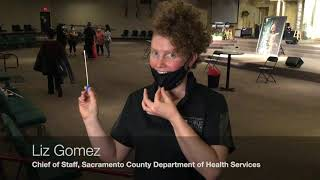 Person holding swab while uncovering nose with face mask.